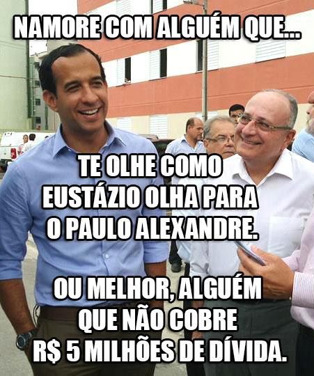"""Meme: Foto do Eustázio com olhar apaixonado pelo Paulo Alexandre Barbosa com os dizeres: """"NAMORE COM ALGUÉM QUE... TE OLHE COMO EUSTÁZIO OLHA PARA O PAULO ALEXANDRE. OU MELHOR, ALGUÉM QUE NÃO COBRE R$ 5 MILHÕES DE DÍVIDA""""."""