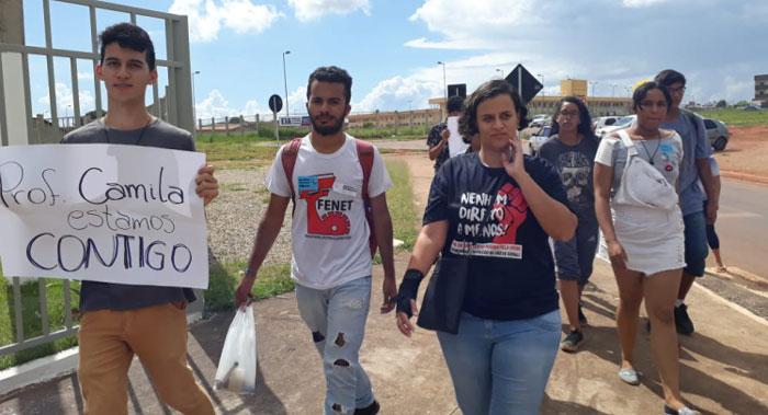 """Foto da professora Camila Marques com seus alunos em volta. Um deles carrega um cartaz escrito """"Prof Camila estamos contigo"""""""