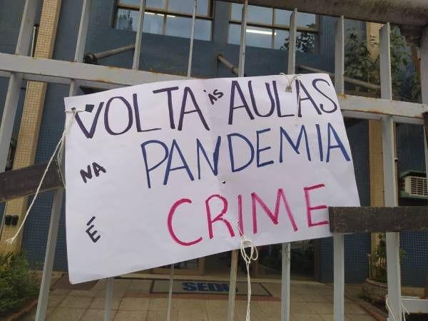 """Foto de um cartaz onde está escrito: """"VOLTA ÀS AULAS NA PANDEMIA É CRIME"""""""