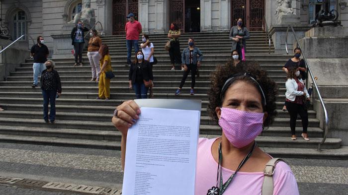 Foto com uma servidora mostrando a carta em primeiro plano e no fundo outras servidoras na escadaria do Paço Municipal respeitando o distanciamento