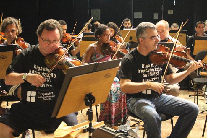 """Músicos tocando no Teatro Coliseu. Todos com a camisa que diz: """"Diga não à terceirização da OSMS! #osmsviva"""""""