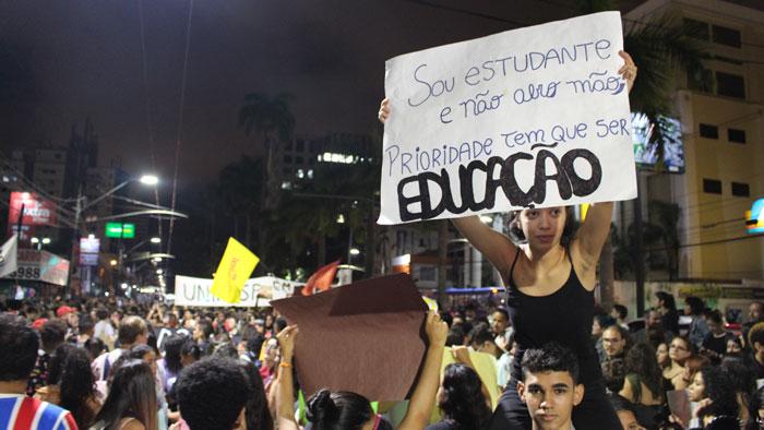 """Foto do ato do dia 15/05. Garota segura cartaz escrito: """"Sou estudante e não abro mão, prioridade tem que ser EDUCAÇÃO"""""""