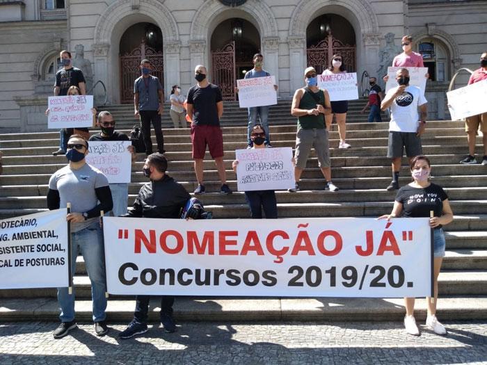 Foto dos manifestantes nas escadarias da Prefeitura respeitando o isolamento