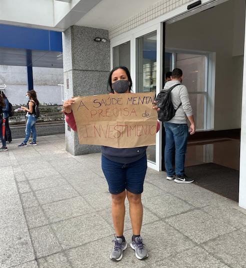 """Foto de uma manifestante com o cartaz: """"A Saúde Mental precisa de investimento"""""""